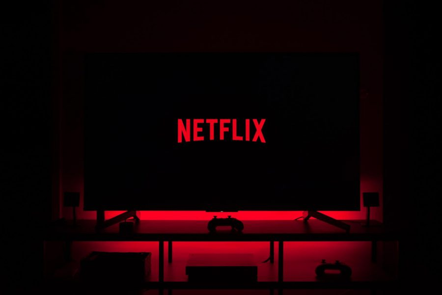 A dark screen shows the red Netflix logo. The background of the screen is illuminated by a red LED light.