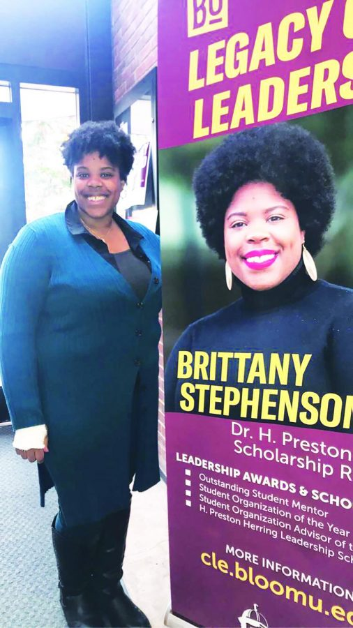 Senior Brittany Stephenson, the recipient of the Dr. H. Preston Herring Scholarship, stands with the poster promoting her achievement in Bakeless.